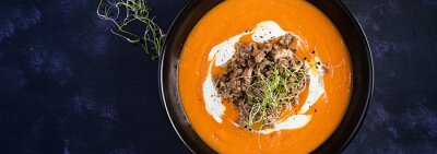 Delicious cream of pumpkin soup with roasted forcemeat made of beef minced meat in a bowl on a dark table. Thanksgiving Day. Top view, banner