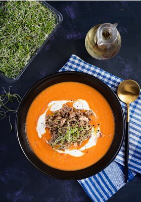 Delicious cream of pumpkin soup with roasted forcemeat made of beef minced meat in a bowl on a dark table. Thanksgiving Day. Top view, overhead