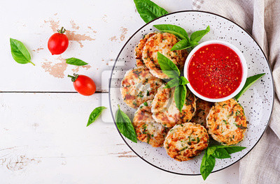Delicious rice and chicken meat patties with garlic tomato sauce. Top view. Diet food. Copy space
