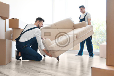 Plakat Delivery men moving sofa in room at new home