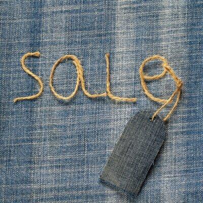 denim tle tkaniny z napisem sprzedaży sznurka w ręku i pustego cennika