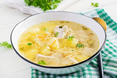 Diet soup. Chicken soup with noodles and vegetables in white bowl.