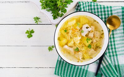 Diet soup. Chicken soup with noodles and vegetables in white bowl. Top view, overhead