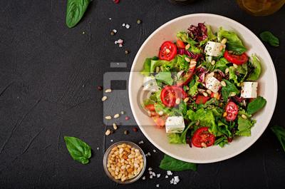Dietetyczna sałatka z pomidorami, fetą, sałatą, szpinakiem i orzeszkami pinii. Widok z góry. Płaskie leżało.