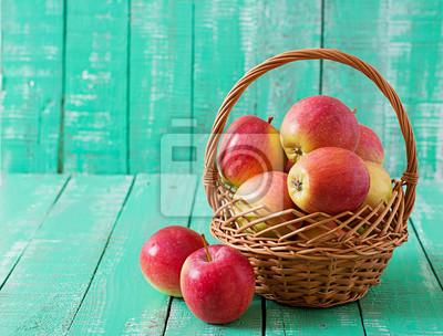 Dojrzałe czerwone jabłka w koszu na jasnym tle drewniane