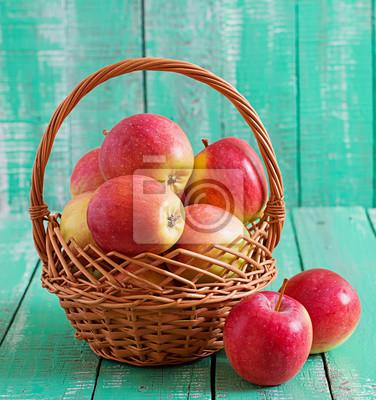 Dojrzałe czerwone jabłka w koszyku na jasnym tle drewnianym