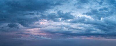 Plakat Dramatic overcast sky at evening panoramic shot. Scenic blue gray clouds before the storm. Scenic cloudscape before the rain. Blue hour stormy cloudscape. Dark thunderstorm sky wide image.