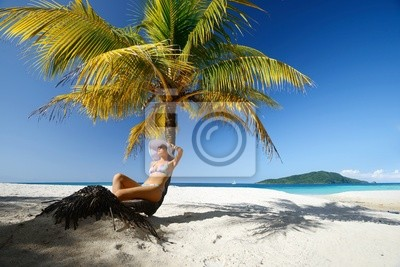 Dreaming kobieta siedzi na plaży pod palmą na beaut