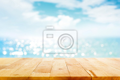 Plakat Drewniany stół blur na rozmycie musujące wody morskiej i latem nieba tle