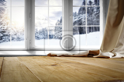Drewniany stół z miejscem na Twój produkt. Zasłona w oknie. Otwórz okno z płatkami śniegu. Krajobraz zimowy las. Poranne słońce.