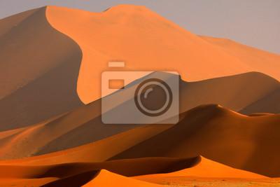 Plakat Duża pomarańczowa diuna z niebieskim niebem i chmurami, Sossusvlei, Namib pustynia, Namibia, afryka poludniowa. Czerwony piasek, największy dun na świecie. Podróżowanie po Namibii.