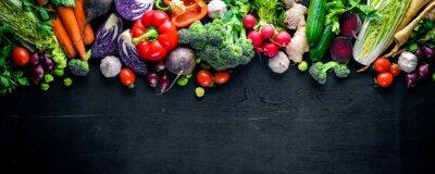 Plakat Duża zestaw żywności ekologicznej. Świeże warzywa surowe. Na czarnej tablicy.