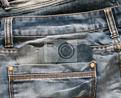 dwa kieszonkowe serca są wycięte z niebieskich dżinsów z kieszeni starego noszonego spodnia