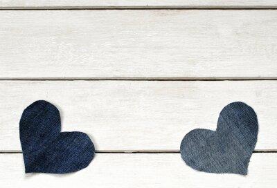 dwa stylowe serca są wycięte z niebieskiego materiału denim leżącego na białym tle drewnianych