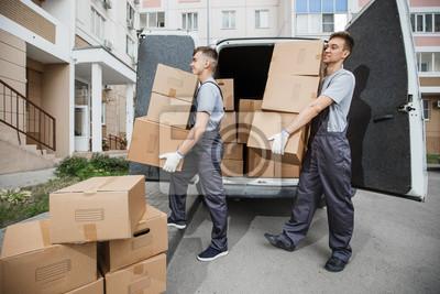 Plakat Dwaj młodzi przystojni uśmiechnięci pracownicy w mundurach rozładowują furgonetkę pełną skrzynek. Blok mieszkalny jest w tle. Przeprowadzka do domu, usługa przenoszenia.