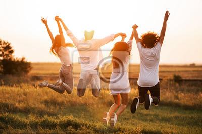 Plakat Dwóch młodych chłopaków i dwie dziewczyny trzymają rękę i skaczą w polu w letni dzień. Widok z tyłu.