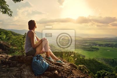 Dziewczyna siedzi na krawędzi urwiska i patrząc na słońce
