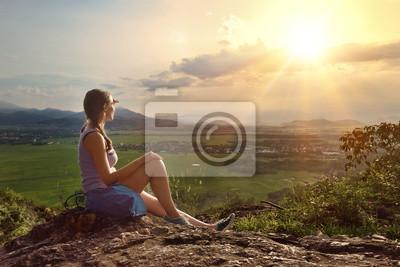 Dziewczyna siedzi na krawędzi urwiska, patrząc na słońce i góry