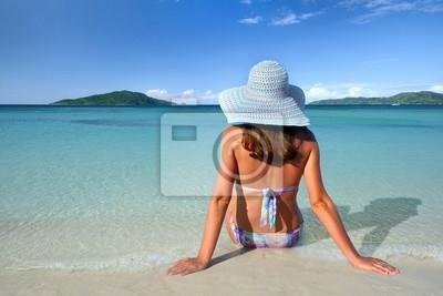 Dziewczyna w kapeluszu letni leżąc na piasku i patrzeć w niebo na