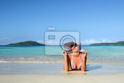 Dziewczyna w kapeluszu letniego leżącego na piasku i patrzeć w niebo na