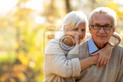 Plakat Elderly couple embracing in autumn park