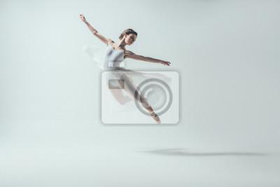Plakat elegancka tancerka baletowa w białej sukni skoki w studio, na białym tle
