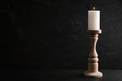 Plakat Elegant candlestick with burning candle on black table. Space for text