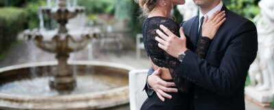Plakat Elegant man in a black suit and Rich woman in black dress hug. Young stylish man and woman in beautiful backyard with fountain on background.