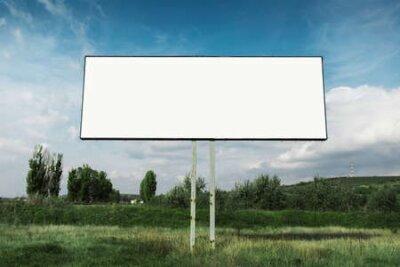 Plakat Empty billboard for advertising poster in green field omn background of blue sky.