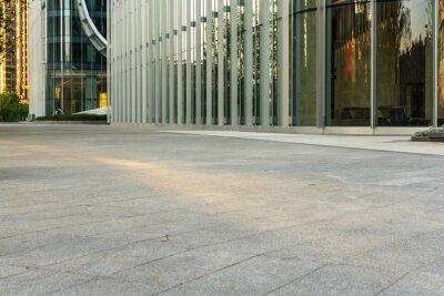 Plakat empty concrete ground floor with modern office buildings.