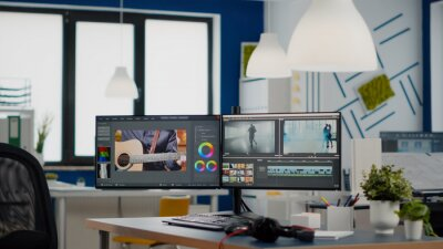 Plakat Empty modern creative agency office with dual monitors setup with processing video film montage. Video editing start up studio company with no people in it and post production software on pc displays
