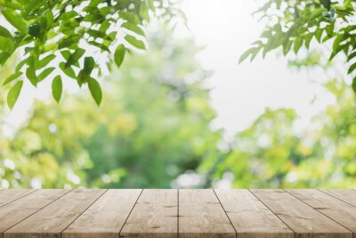 Plakat Empty wood table top and blurred green tree in the park garden background - can used for display or montage your products.