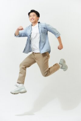 Plakat Energetic happy young Asian man in casual clothes jumping, studio shot isolated