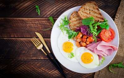 English breakfast - fried egg, beans, tomatoes, sausage,ham and toast. Top view, flat lay, overhead