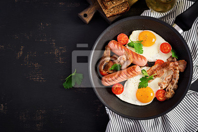 English breakfast - fried egg, tomatoes, sausage and bacon. Top view