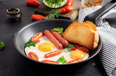 English breakfast - fried egg,  tomatoes, sausage,  and toasts. Top view