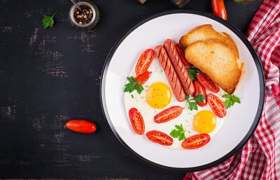 English breakfast - fried egg,  tomatoes, sausage,  and toasts. Top view, overhead