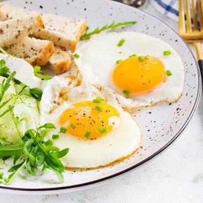 English breakfast - fried eggs, feta cheese, cucumber and arugula. American food.