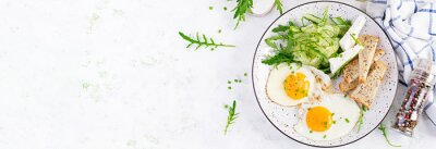 English breakfast - fried eggs, feta cheese, cucumber and arugula. American food. Top view, overhead, banner