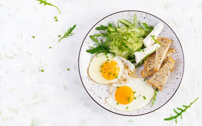 English breakfast - fried eggs, feta cheese, cucumber and arugula. American food. Top view, overhead, copy space