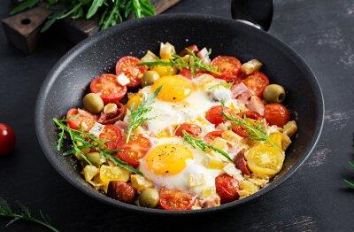 English breakfast - fried eggs, ham, tomatoes and arugula. American food.