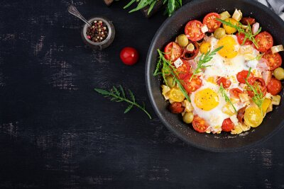 English breakfast - fried eggs, ham, tomatoes and arugula. American food. Top view, overhead, copy space