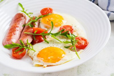 English breakfast - fried eggs, sausages, tomatoes and arugula. American food.