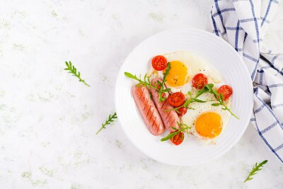 English breakfast - fried eggs, sausages, tomatoes and arugula. American food. Top view, overhead, copy space