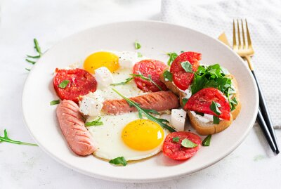 English breakfast - fried eggs, sausages, tomatoes and feta cheese. American food.