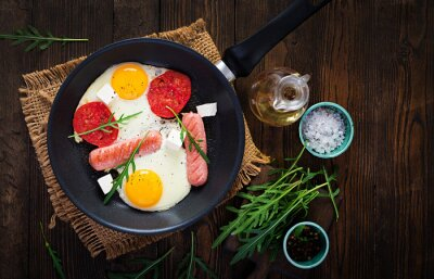 English breakfast - fried eggs, sausages, tomatoes and feta cheese. American food. Top view, overhead, copy space