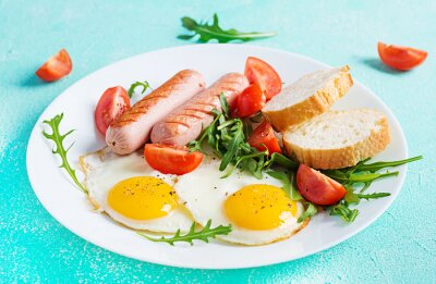 English breakfast - fried eggs, sausages, tomatoes and fresh arugula. American food.