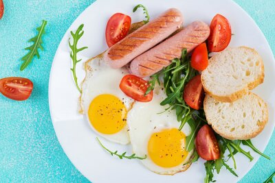 English breakfast - fried eggs, sausages, tomatoes and fresh arugula. American food. Top view, flat lay