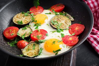English breakfast - fried eggs, tomatoes and eggplant. American food.