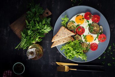 English breakfast - fried eggs, tomatoes and eggplant. American food. Top view, overhead, copy space